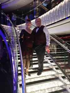 me and my wife standing on brightly lit open stairs dressed in 1920's garb